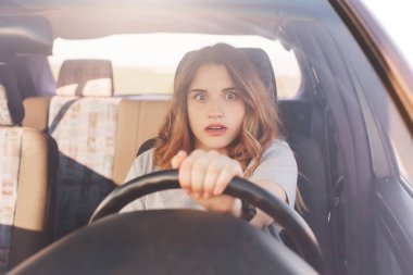Terrified young cute female looks with depressed scared expression in front as drives car, has collision with other transport or accident on road, being inexperienced driver. Problems on road