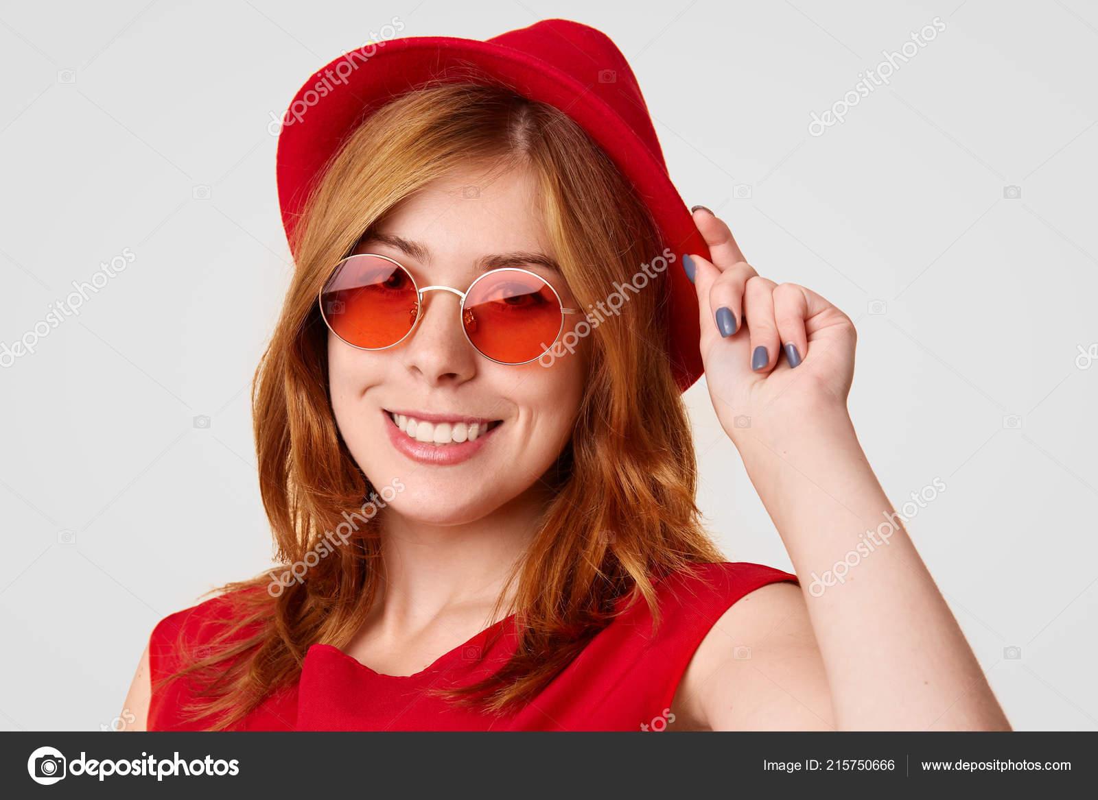 ec2ffc0c53a9e Hermosa mujer con estilo se encuentra lateralmente toca moda sombrero rojo