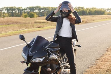 Photo of attractive female biker dressed in leather jacket, wears helmet, poses on motorbike against road background, likes her hobby, has rest for minute, has active rest. People, transport and speed