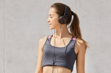 Portrait of caucasian pretty woman listening to music while having workout in gym, has headphones, posing in studio, stands with closed eyes, isolated over gray background. Health care concept.