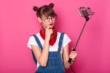 Indoor shot of serious thoughtful black haired model standing isolated over pink background, wearing denim overalls, red bandana, white t shirt and round eyeglasses. People and life concept.