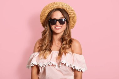 Close up portrait of beautiful young woman with toothy smile, being in black sunglasses, shirt with bare shoulders and hat, model posing with happy facial expressio over rosy studio background.