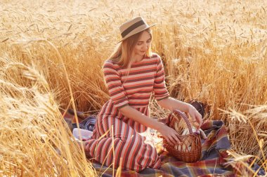 Portrait of attractive tender young lady spending time alone at wheat field, sitting on blanket, touching basket with hands, going to have meal around nature, wearing straw hat and casual dress.