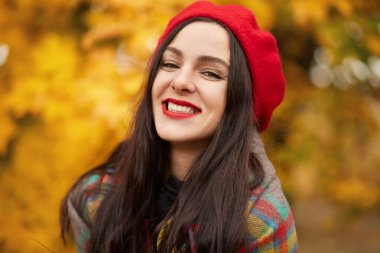 Autumn portrait of happy lovely and beautiful Caucasian young woman in forest in fall colors, attractive female dresses red beret and wrapped checkered blanket, poses smiling in autumn park.