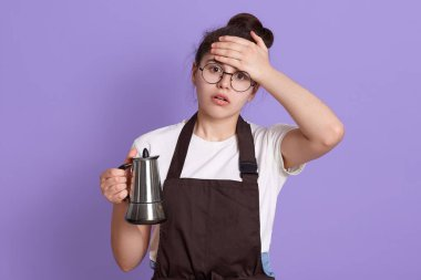 Tired attractive teenage girl wearing white t shirt and brown apron, holding tea or coffee pot in hands, looks tired and astonished, keeping hand on forehead, standing against lilac wall.