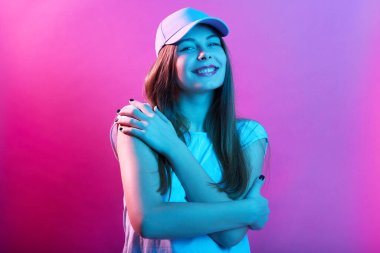 Smiling woman against rose neon wall embracing herself and looking directly at camera, wearing casual t shirt and baseball cap, expressing calm, loves herself.