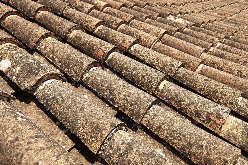 Detail and perspective of a grungy old tiles roof in south Europe