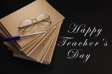 teachers day greeting card with notebooks, pen and eyeglasses on black background with copy space