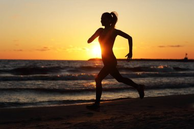 Woman running alone at beautiful dusk on the beach