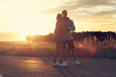 Young couple jogging in the suberbs after sunset