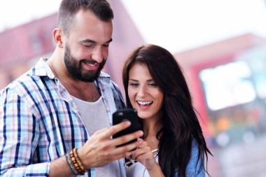 Happy couple using smartphone in city in rainy day