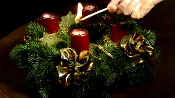 Adventskranz mit brennender Kerze und Weihnachtsmann mit Kuchen auf Drehtisch