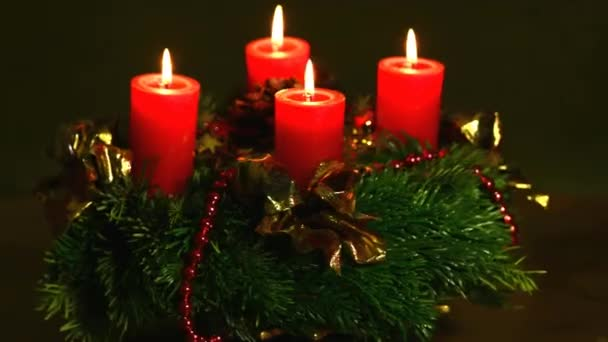 Falling snow and Advent wreath with burning candles