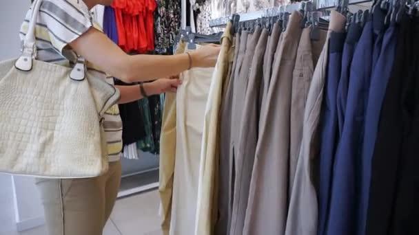Žena nakupování vypadat přes šaty na ramínkách v módní oblečení butik