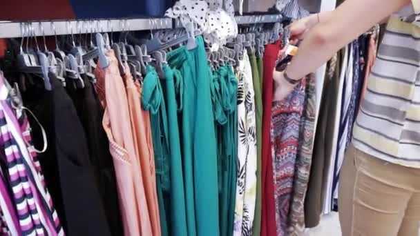 Woman shopping look over dresses on hangers in fashionable clothes boutique shop
