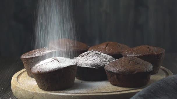 Pekař poprašování práškového cukru nad lahodnými čokoládovými muffiny