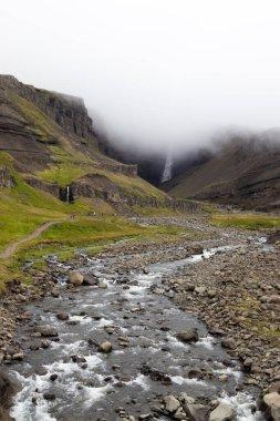 """Картина, постер, плакат, фотообои """"мистический вид водопада хенгифосс в облаке, восточная исландия. водопад с красным полосатым камнем в тумане. летняя прогулка. красивый исландский пейзаж. картины пейзаж"""", артикул 410449920"""