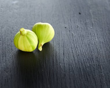 The green FIG is on a black wood table with natural light.