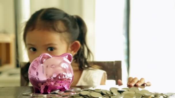 Roztomilá dívka, uvedení mincí do prasátko bank v tuzemsku