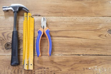 hammer, folding ruler and nippers on wooden background