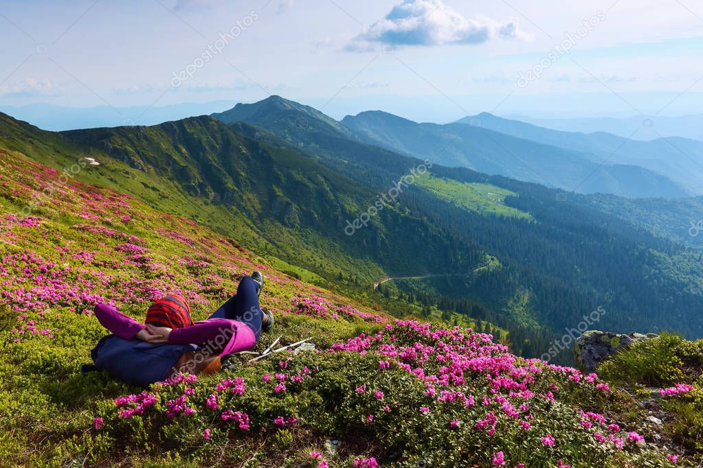 The landscape with the high mountains. Sky with clouds. Forest road. On the lawn of the rhododendrons the girl is laying. Eco tourism. Charming summer day.