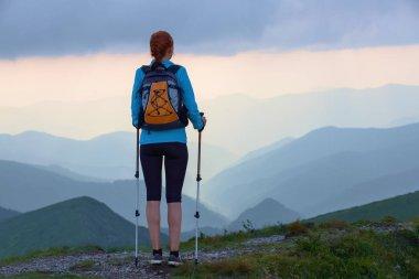 """Картина, постер, плакат, фотообои """"туристка с мешком и отслеживающими палками остается на лужайке. прекрасное облачное небо. солнечные лучи падают на горы. летняя сцена. время эко-туризма ."""", артикул 209156160"""