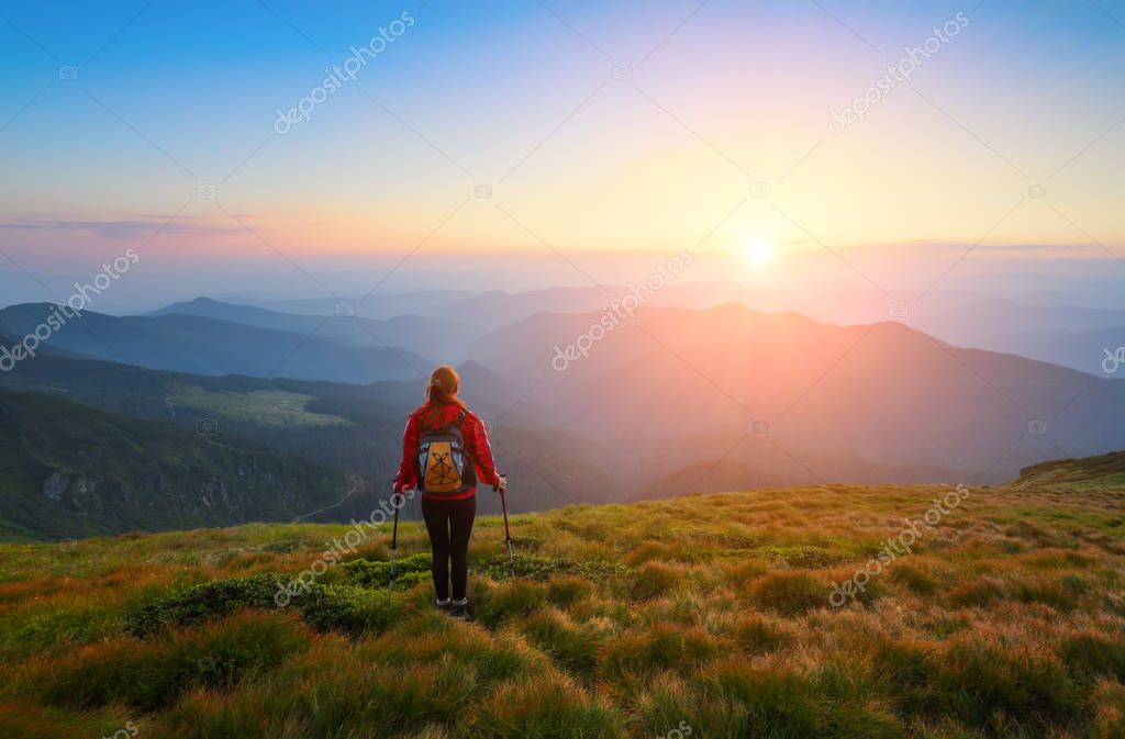 Sporty girl with back sack is standing at the lawn and watching on the endless cast of mountains landscape in the sunny day.