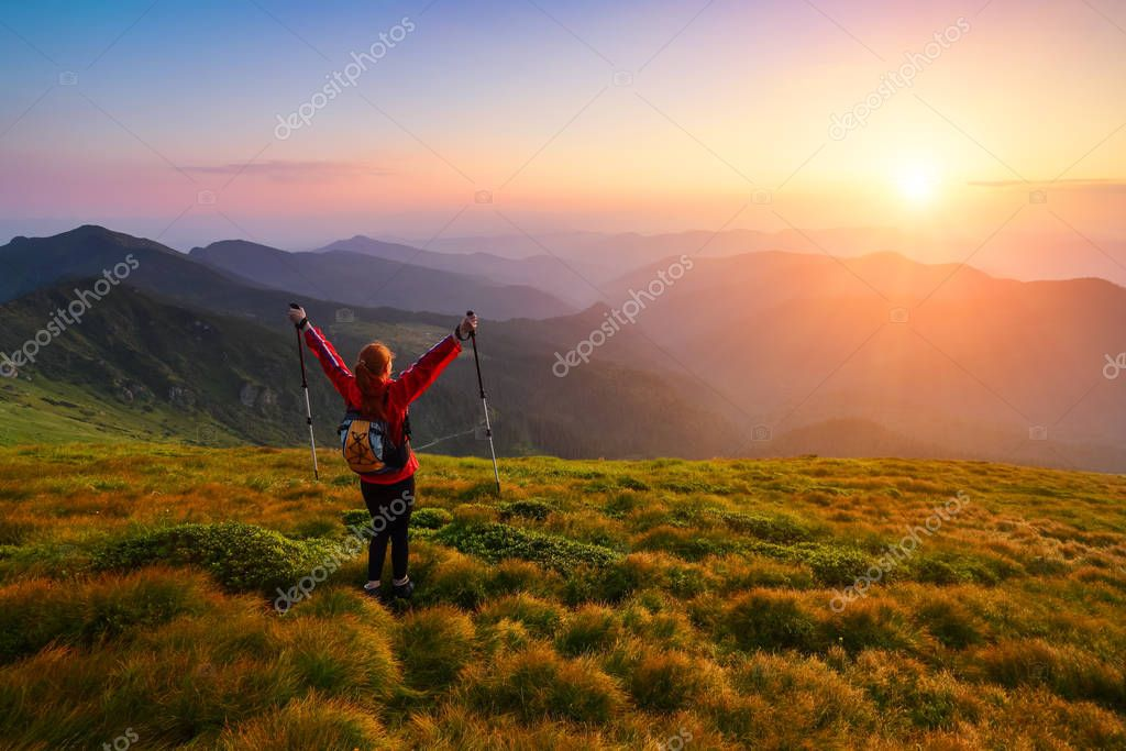 Sporty girl with back sack is standing at the lawn and watching on the endless cast of mountains landscape in the sunny day. Fantastic summer scenery