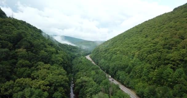 4 k letecké stopáže auta jízdy po klikaté horské silnici průchodu lesem v Soči, Rusko. Lidé, kteří cestují, výlet na křivolaké silnici přes krásnou krajinu