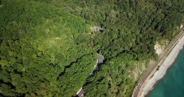 4 k letecké stopáže auta jízdy po klikaté horské silnici průchodu lesem v Soči, Rusko. Lidé, kteří cestují, výlet na křivolaké silnici přes krásnou krajinu.