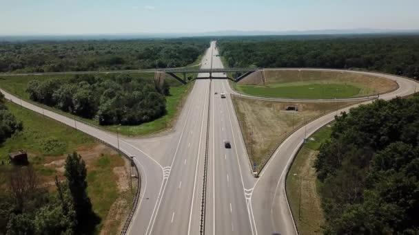 Letecký pohled na dálniční křižovatku na venkově se stromy a kultivovanými oblastmi.