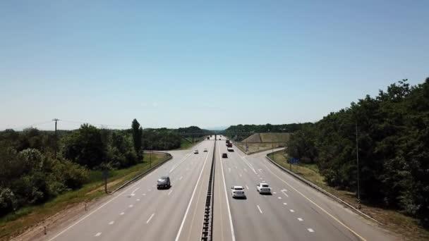 Přeletět přes dálniční křižovatku na venkově se stromy a kultivovanými oblastmi.