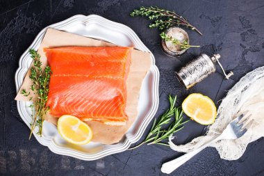 salmon fish fillet on silver plate with lemon and thyme, top view