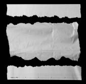 Fotografia Tre pezzi di carta strappata sul nero