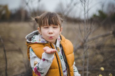 Adorable girl blowing kisses on early spring