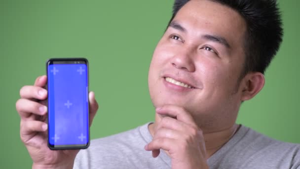 Young handsome overweight Asian man against green background