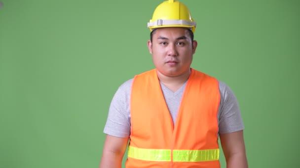 Mladý pohledný nadváhu Asiat stavební dělník proti zeleným pozadím