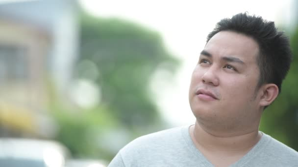 Fiatal jóképű túlsúlyos ázsiai ember az utcán szabadban