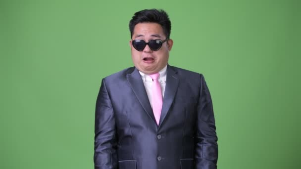 Young handsome overweight Asian businessman against green background