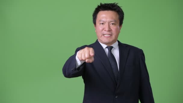 Mature Japanese businessman against green background
