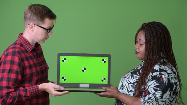 Overweight African woman and young Scandinavian man together against green background