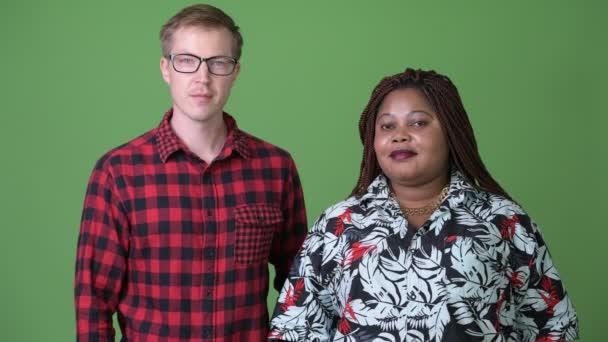 S nadváhou Afričanka a skandinávské mladík společně proti zeleným pozadím