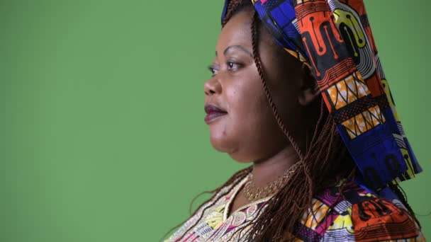 Overweight beautiful African woman wearing traditional clothing against green background