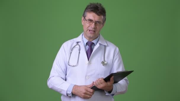 Ältere gut aussehende Mann Arzt vor grünem Hintergrund