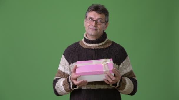 Starší pohledný muž nosí rolák zelené pozadí