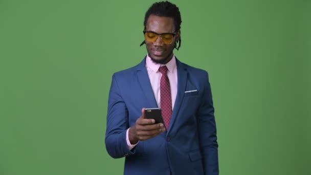 junger schöner afrikanischer Geschäftsmann mit Dreadlocks vor grünem Hintergrund