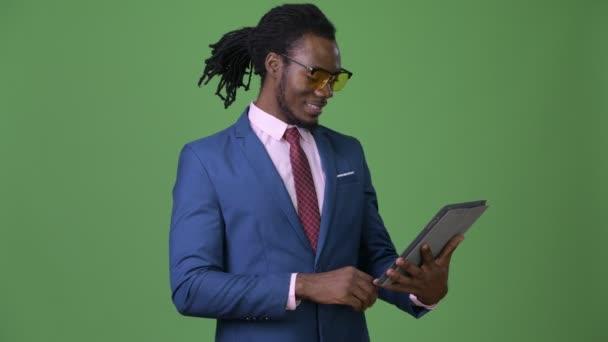 Mladý pohledný africký podnikatel s dredy před zeleným pozadím
