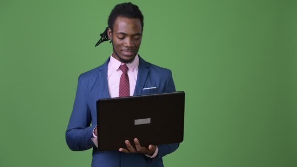 Young handsome African businessman with dreadlocks against green background