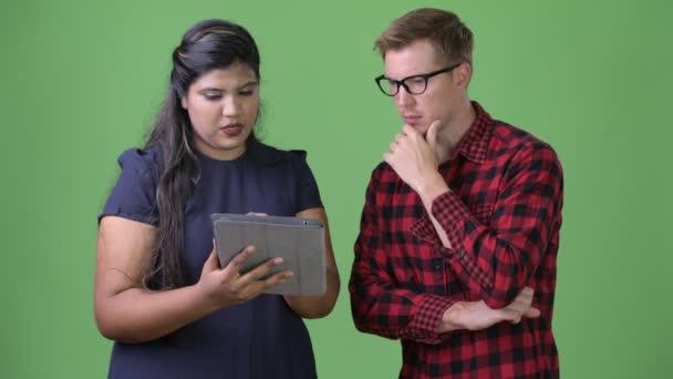 Studio záběr mladá nadváhou krásné indické podnikatelka a mladý pohledný skandinávské podnikatel společně proti chroma klíč se zeleným pozadím