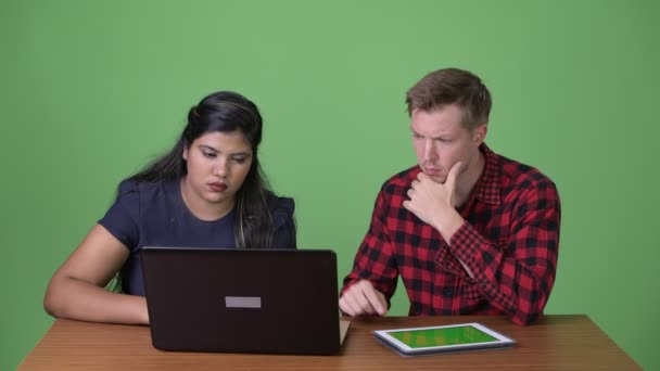 Young multi-ethnic business couple together against green background